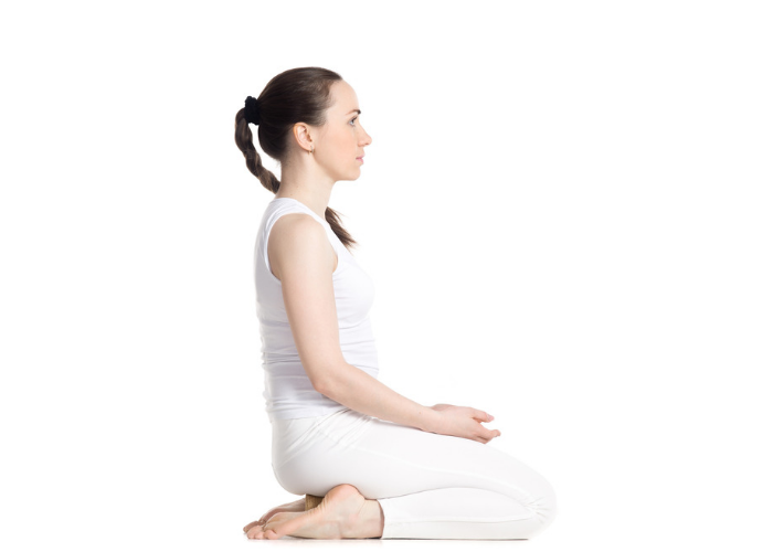 Woman dressed in white doing the rock pose during Kundalini yoga practice