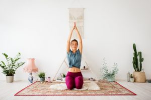 Woman practicing Kundalini yoga at home