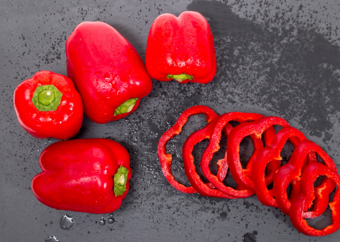 Whole and sliced red peppers that are rich in the amino acid leucine, laid out on a grey table