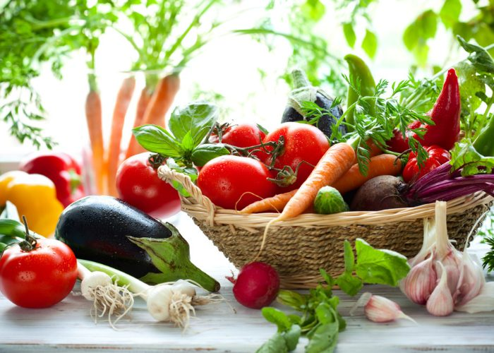 Vegetables such as tomatoes, carrots, eggplant, garlic, and spring onions rich in the amino acid methionine, in a wooden basket and also on a table