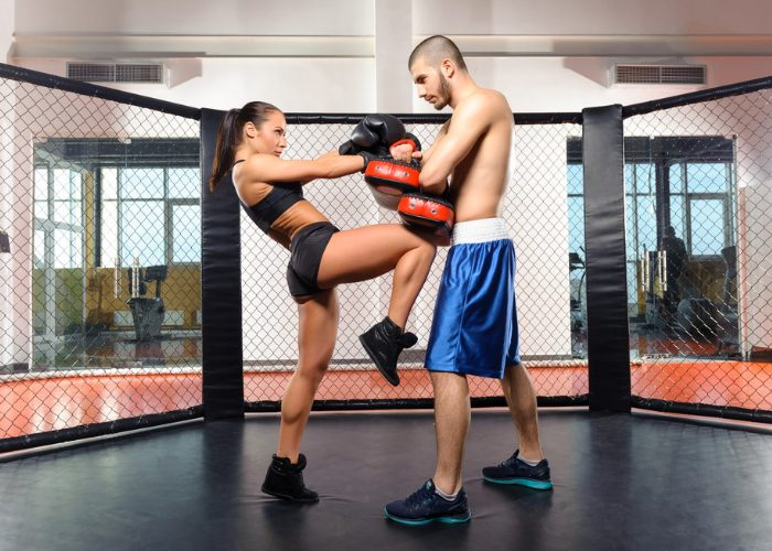 A woman practicing mixed martial arts in a MMA ring with her partner