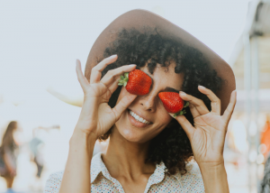 Smiling woman outdoors holding up two strawberries to her eyes