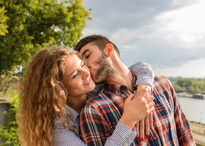 A happy heterosexual couple outdoors, with the man kissing the woman on the cheek as she huge him from behind