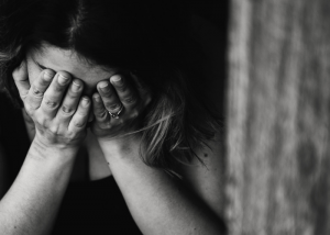Woman holding her head in her hands in sadness