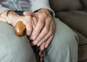 Close up of an old woman's hands holding onto her cane