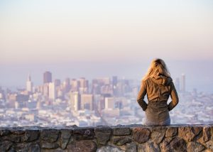 The back of a nulliparous woman sitting on a wall overlooking a city