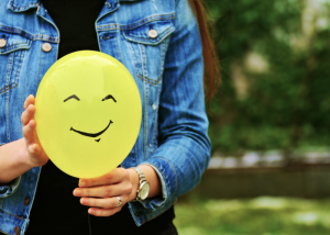 Nulliparous woman in denim jacket holding onto a yellow balloon with a smiley face drawn on it