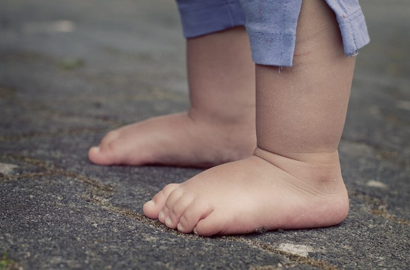 Closeup of feet of a young toddler in blue shorts barefoot on the ground