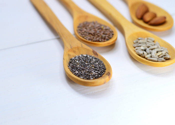 Different nuts and seeds rich in the amino acid phenylalanine, laid out on wooden spoons on a white table