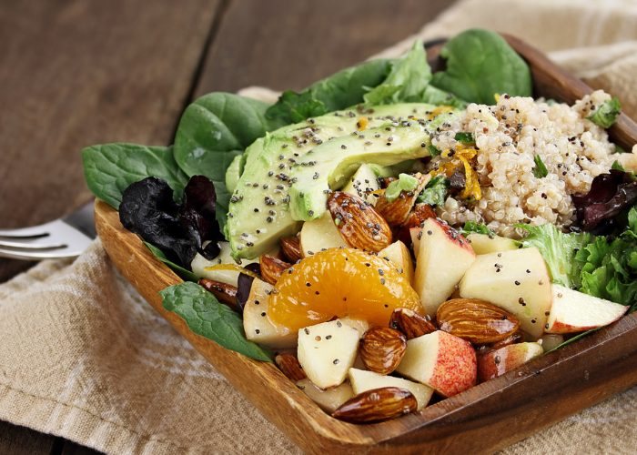 A plant-based dish of spinach, avocado, nuts, and sliced fruit on a wooden plate