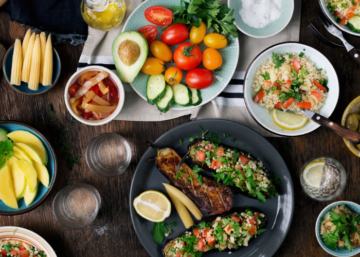 A table filled with different plant-base dishes such as grilled eggplant, fresh tomatoes, avocado, and quinoa