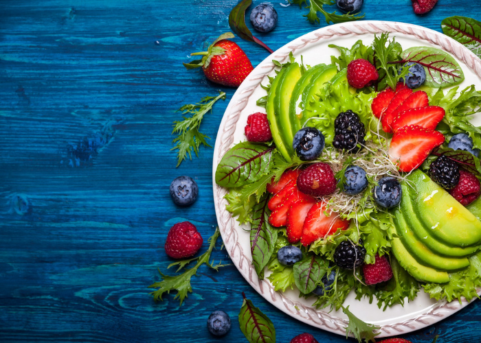 A plate of fresh green salad with avocados, strawberries, and blueberries, on a blue wooden table