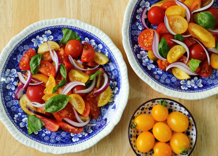 Two plates of mixed red and yellow tomato salads with sliced onion and basil