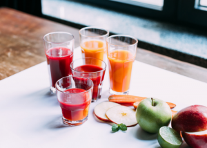Tall gasses of fresh fruit juice, with whole fresh fruits and sliced fruits beside it on a white table