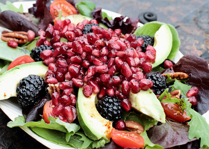 Fresh plant-based diet salad with mixed greens, walnuts, blackberries, tomatoes, topped with pomegranate.