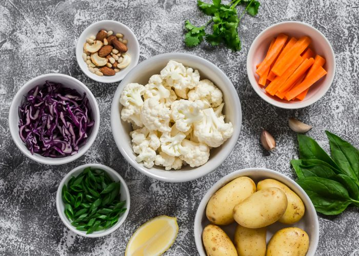 Different bowls with plant-based foods such as cauliflower, potatoes, carrots, nuts and cabbage, on a grey background