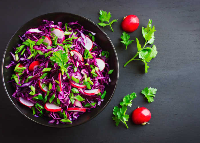 A bowl of purple cabbage, sliced small red radishes, and green parsley leaves in a black bowl on a black table