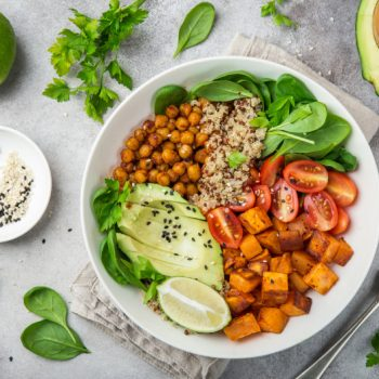 Top down shot of a healthy vegan salad bowl with avocado, sweet potato, spinach, tomatoes, chickpeas, lime, cherry tomatoes, and grains against a grey background with other ingredients laid out neatly