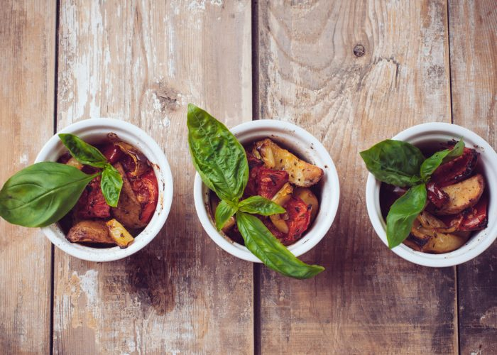 Three small ramekin bowls filled with grilled vegetables topped with fresh basil sprigs