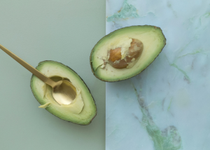 Two halves of an avocado, one set against a pastel olive green background and the other on a marble green background.