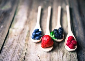 Four wooden spoons filled with prebiotic-rich berries on a wooden table