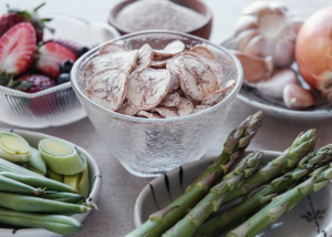Different prebiotic rich foods like dried banana, asparagus, onions, garlic, berries on a table