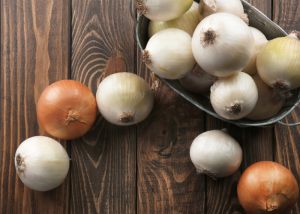 Prebiotic-rich onions in a metal tub on top of a wooden table