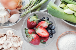 Prebiotic foods such as strawberries, onions, garlic in small dishes on a table