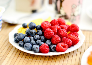 Close up of a plate of blueberries, raspberries, and oranges