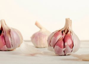 Three whole garlic bulbs with cloves with on a white surface