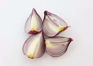 Four quarters of a prebiotic-rich onion on a white surface