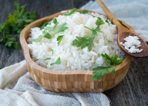 Prebiotic-rich white rice in a wooden bowl with parsley sprinkle on top of it