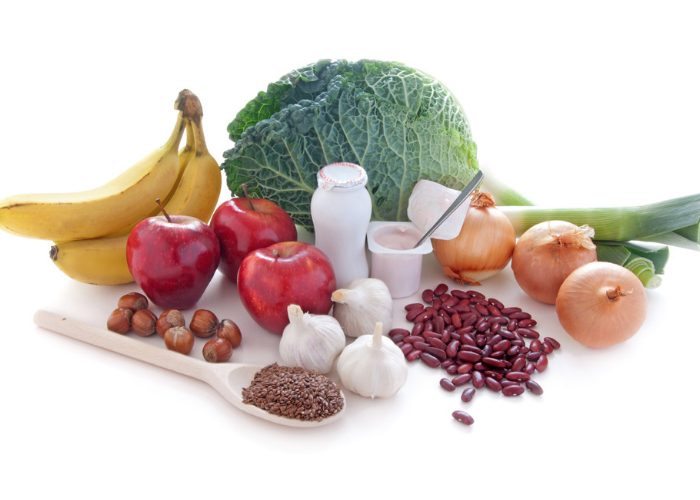 different prebiotic and probiotic foods such as bananas, apples, kidney beans, yogurt, onions, garlic etc. on a white surface