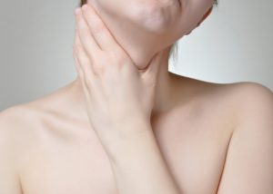 Woman with head tilted to one side holding her neck in pain