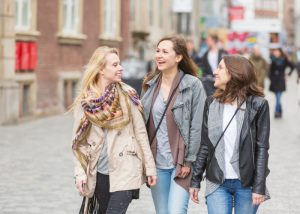 A group of three young women walking down a street and chatting with each other