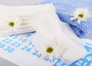 Sanitary pads, blue towels, and white flowers on top of a calendar