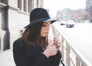 A young woman in a black hat and black coat lighting a cigarette