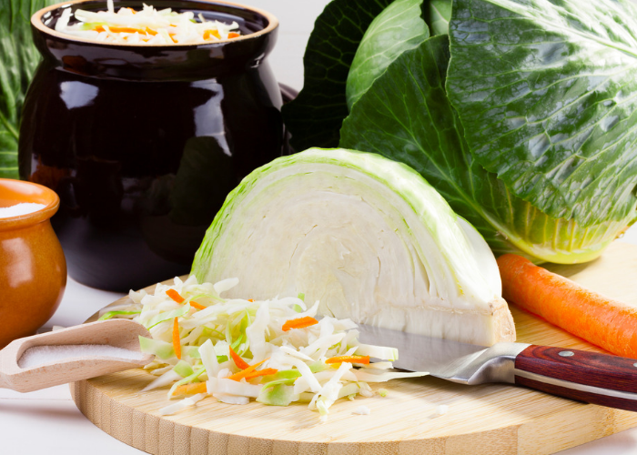 Sliced cabbage and a half cabbage on a chopping board with knife, with pots of sauerkraut in the background