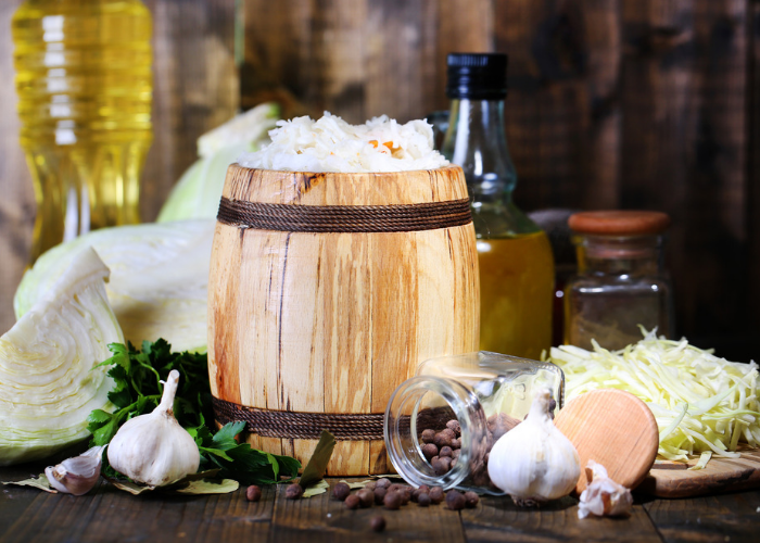 Freshly made sauerkraut in a small wooden barrel with ingredients like garlic, cabbage, oil, and spices around it on the wooden table