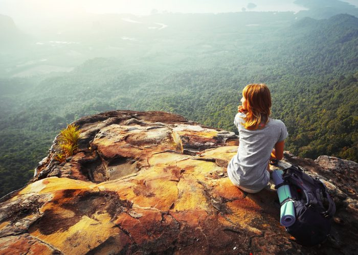 Solo woman backpacker sitting on top of a cliff looking down at the forests below