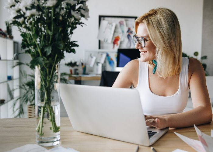 Woman smiling while typing on her laptop in her home office