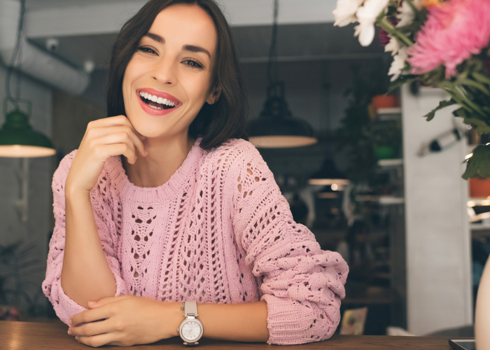 Woman in pink knitted sweater sitting at a cafe smiling