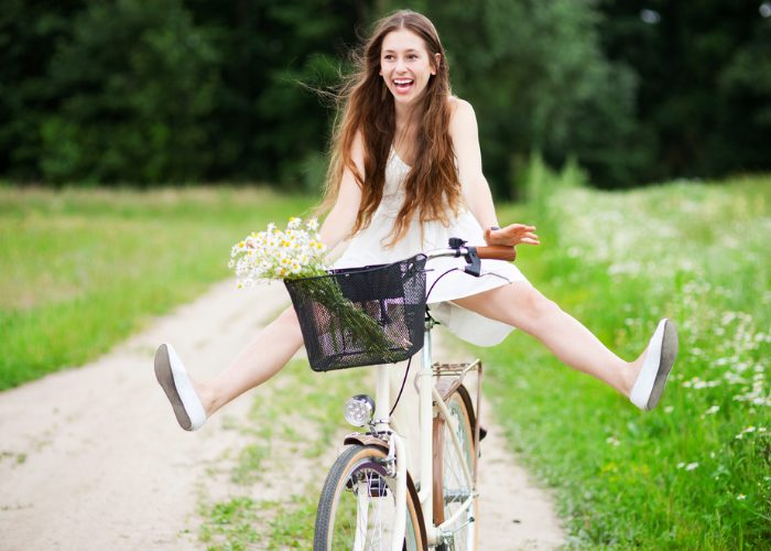 Young woman with a big smile riding a bicycle with her legs up in the air