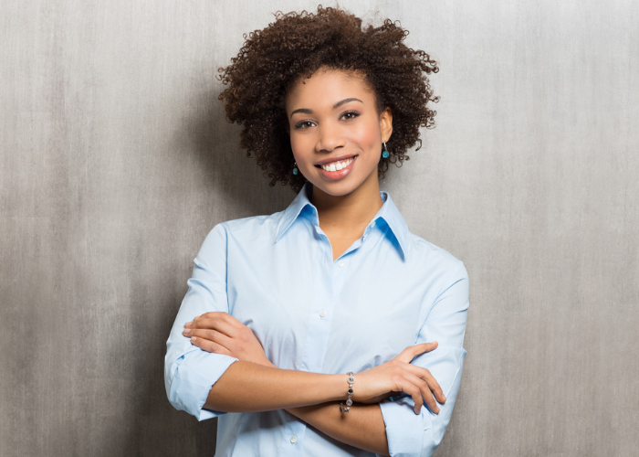 Confident African American woman smiling in a blue shirt with her arms crossed over in front