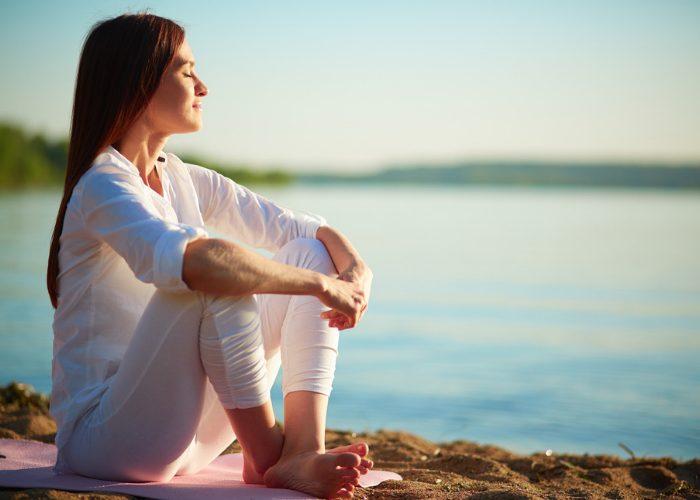 Peaceful and content woman sitting by a lake with her eyes closed and smiling