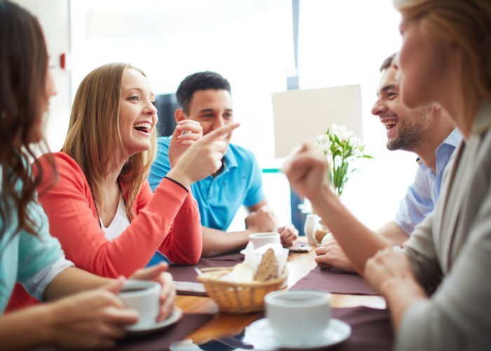 Young woman chatting and laughing with friends at a cafe