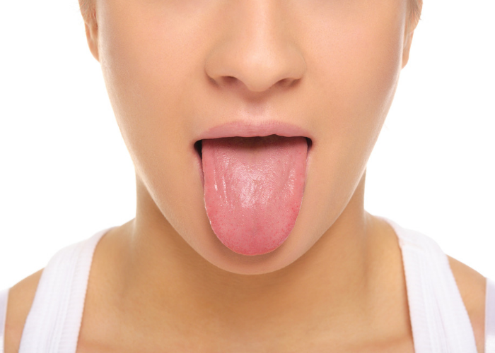 Close up of a woman's face with her tongue sticking out to do the  breathing exercise simhasana