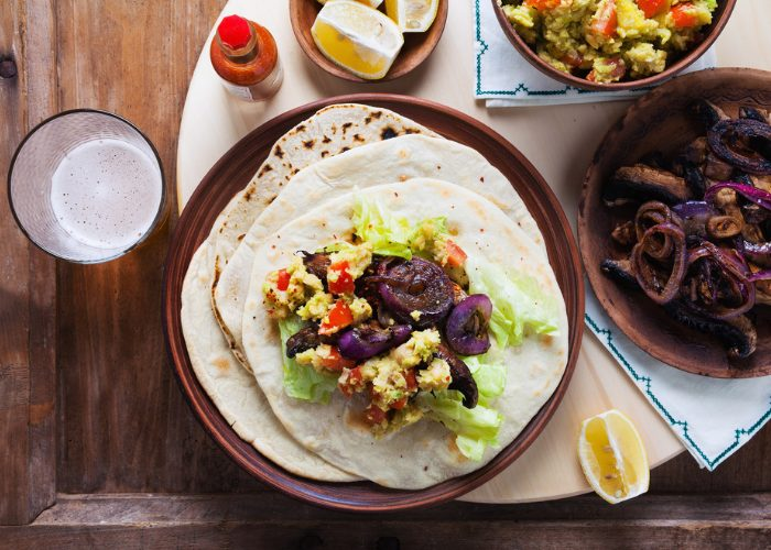 Plant-based meal of spiced mushroom fajitas set on a wooden table with other plates of fillings beside it
