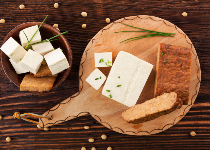 Tofu and tempeh rich in the amino acid threonine, laid out on a wooden board and wooden bowl on a wooden table