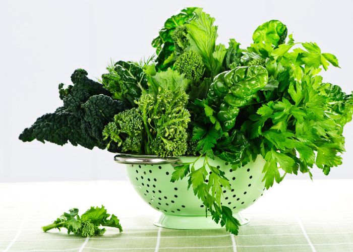 Leafy greens rich in the amino acid tryptophan, sitting in a green colander on a green table